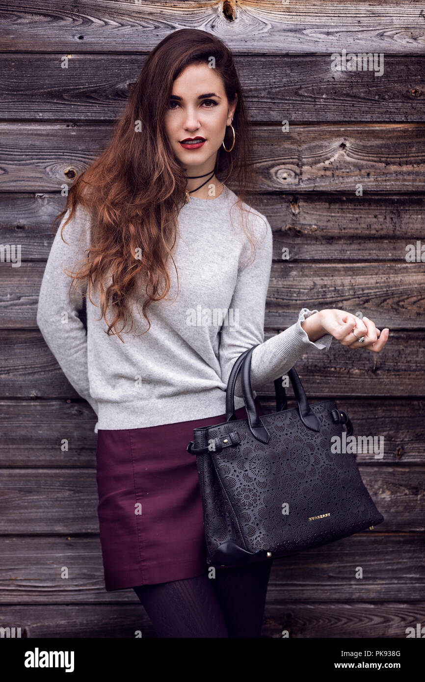 A young attractive woman holding a handbag as she poses for the camera - Stock Image