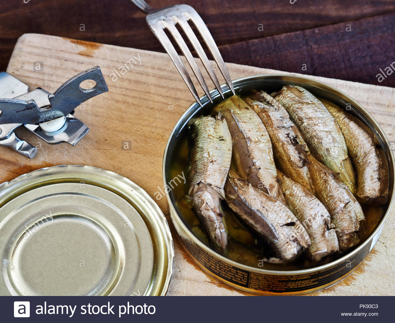 Open tin of smoked sprats in oil, with fork and  tin opener - Stock Image