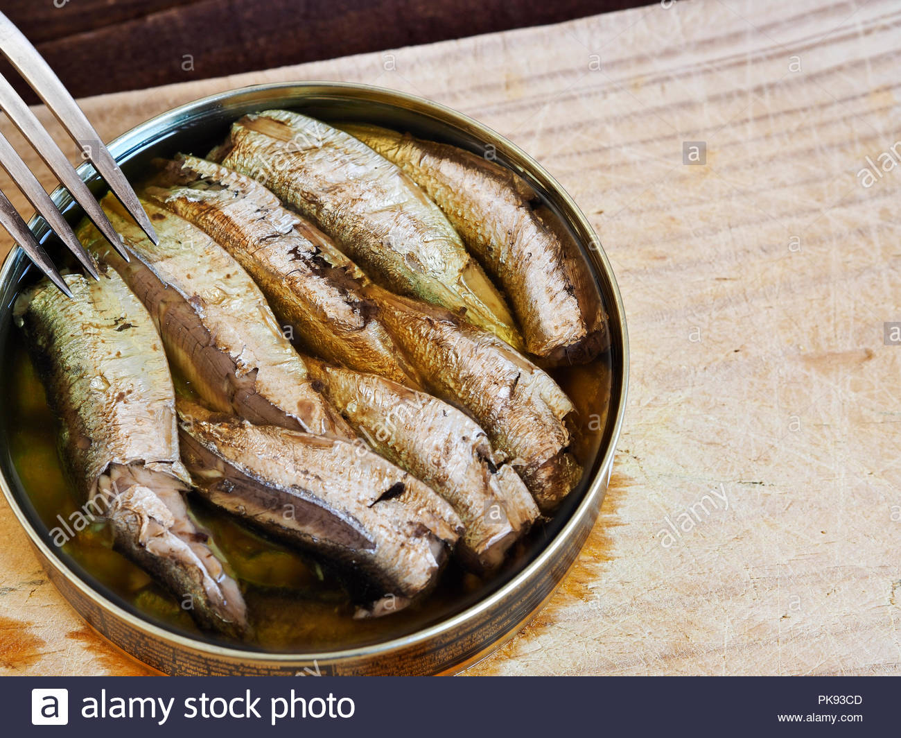 Open tin of smoked sprats in oil, with fork and copy space - Stock Image