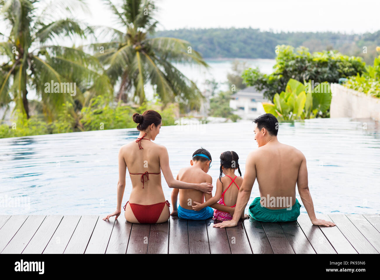 Happy young family sitting side by side at the pool - Stock Image