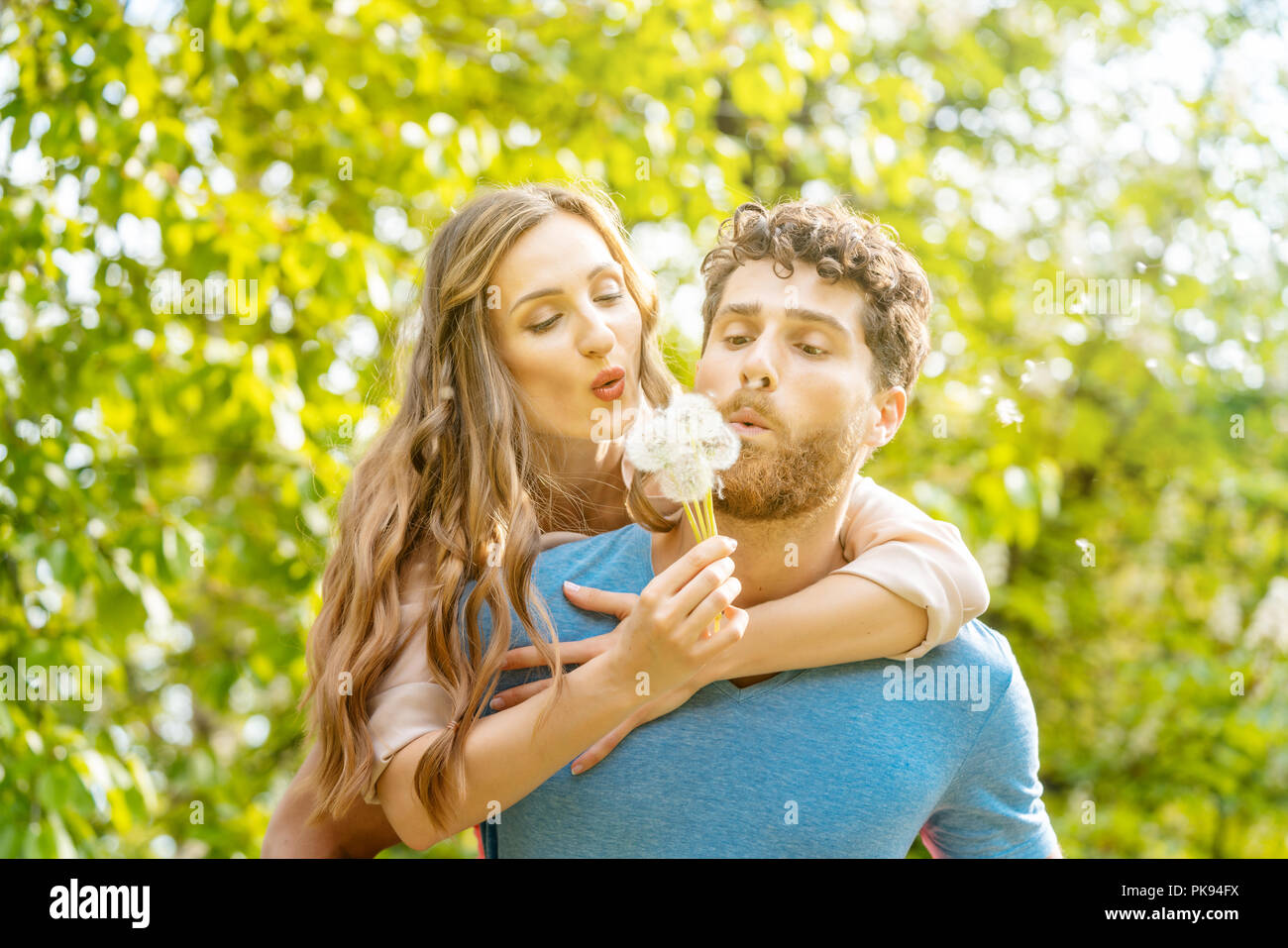 Woman and man on a meadow in romantic mood - Stock Image