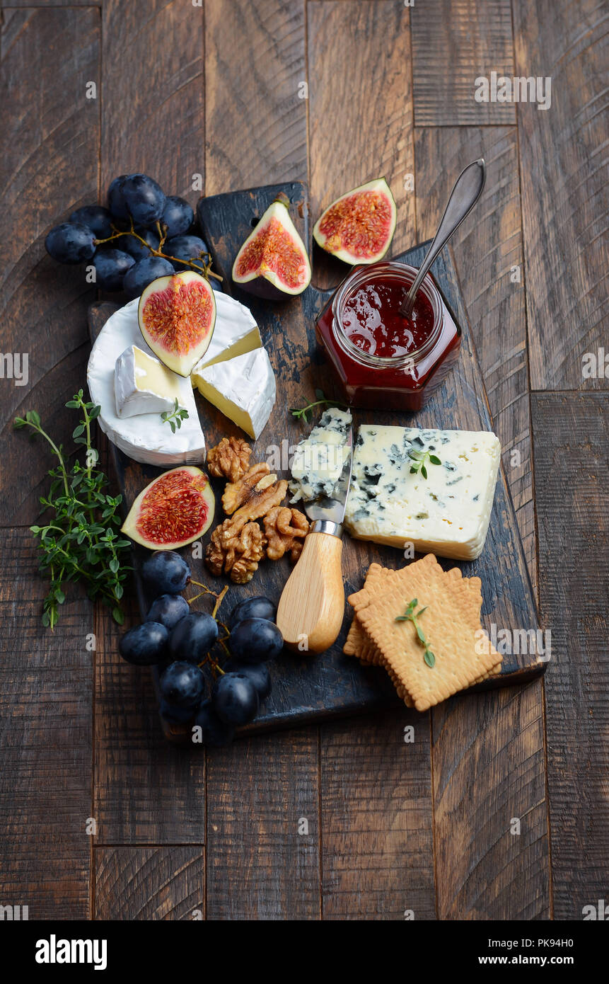 Cheese plate with grapes, figs, crackers, honey, plum jelly, thyme and nuts, selective focus. - Stock Image