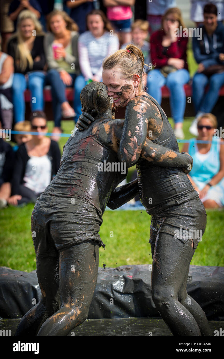 Two women mud wrestling at a mud fighting competition at The LowLand Games  in Thorney Somerset