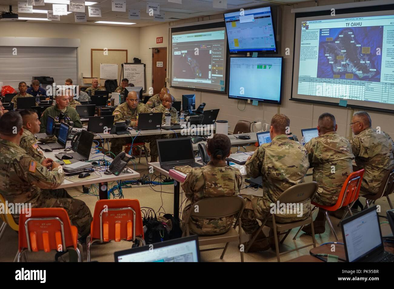 Service members with Joint Task Force 5-0 receive a daily commander's update brief, August 25, 2018 at the Hawaii Army National Guard Center at Diamond Head, Honolulu Hawaii, August 24, 2018. JTF 5-0 is a joint task force led by a dual status commander that is established to respond to the effects of Hurricane Lane on the state of Hawaii. The members of the task force remain committed to monitoring the effects and incidents across the state of Hawaii to respond to any requests made by Local and state authorities through FEMA. () - Stock Image