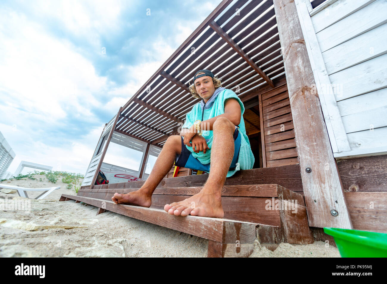 The surfer sits on the terrace on the beach looking out into the distance. - Stock Image