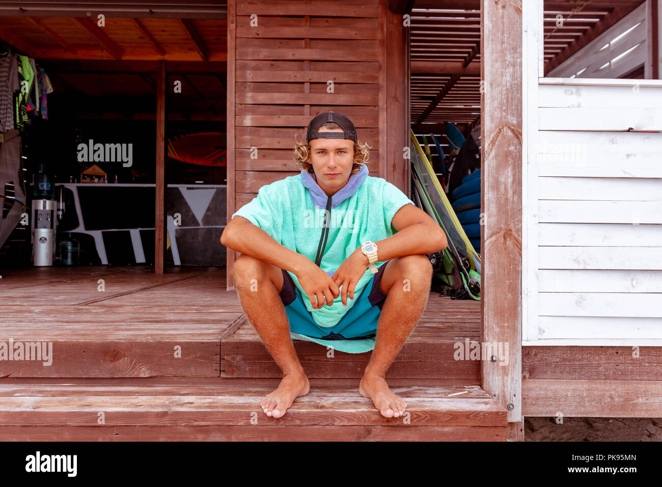 The surfer sits on the terrace on the beach looking out into the camera. - Stock Image
