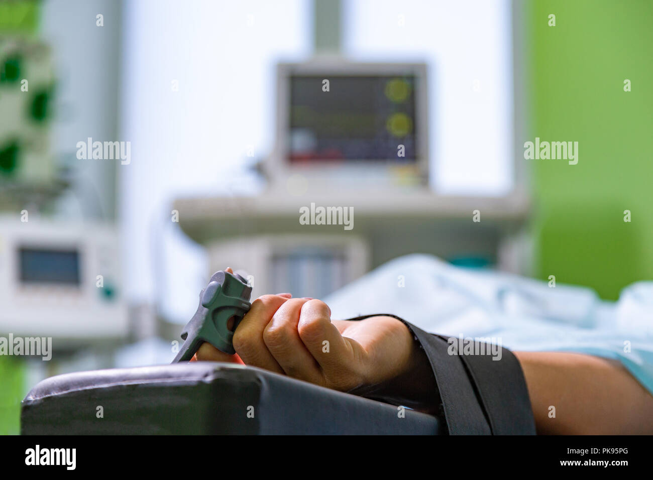 Patients hand with a sensor on the blurry background of the group of doctors in the operating room. Close up, Selective focus - Stock Image