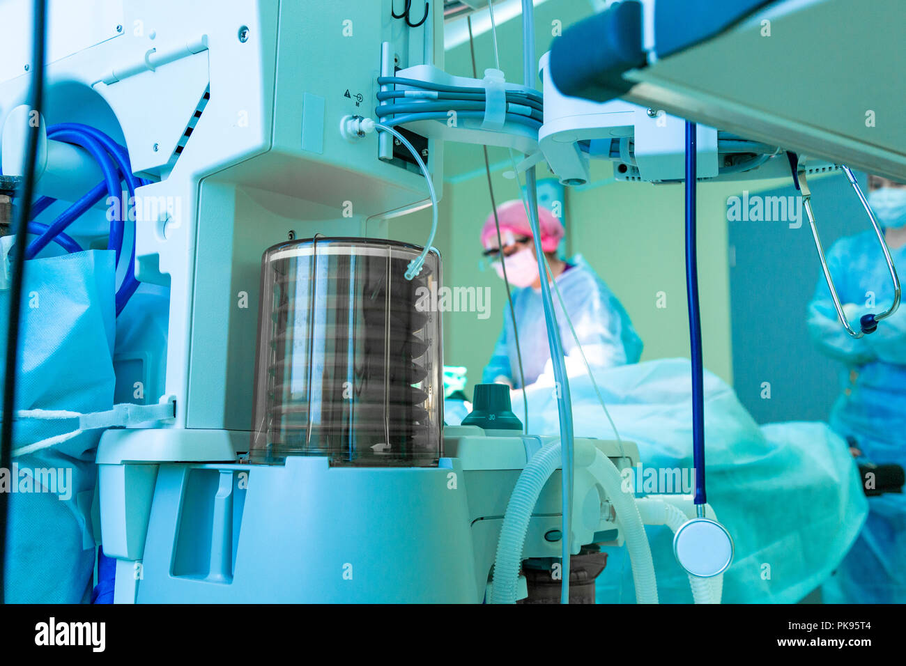 Fragment of breathing apparatus in the operating room, blurred background with team surgeon at work in hospital during their work. - Stock Image