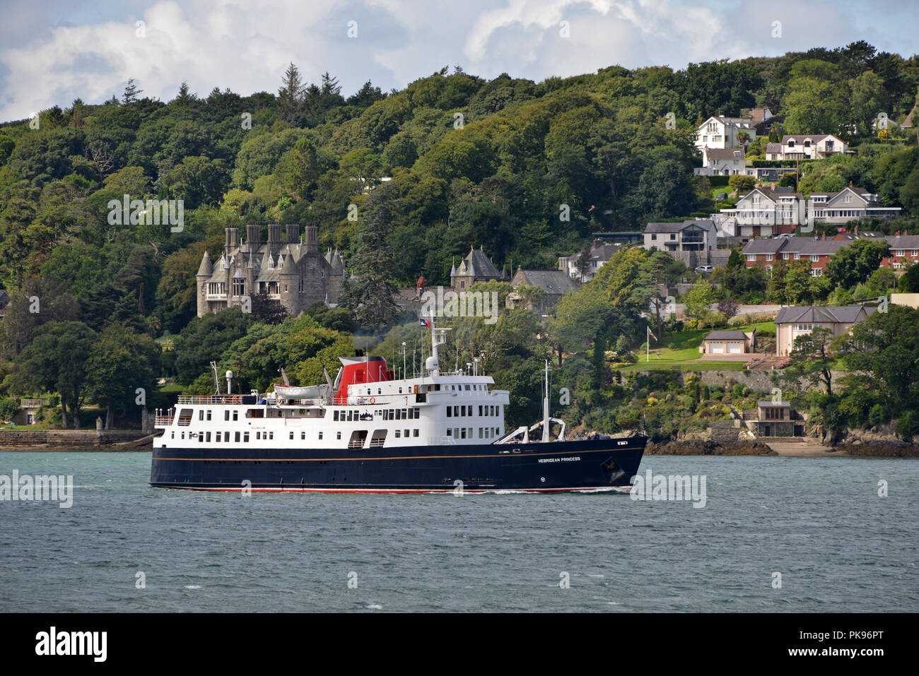Hebridean Princess cruising the Menai Straits with the enchanting French-style Château Rhianfa Hotel astern - Stock Image