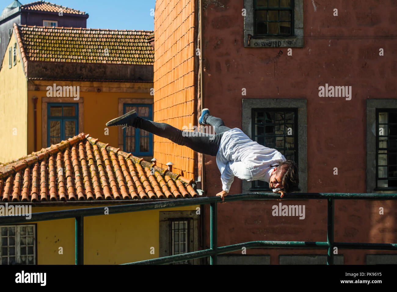 Young man engaged in parkour in the old city. - Stock Image