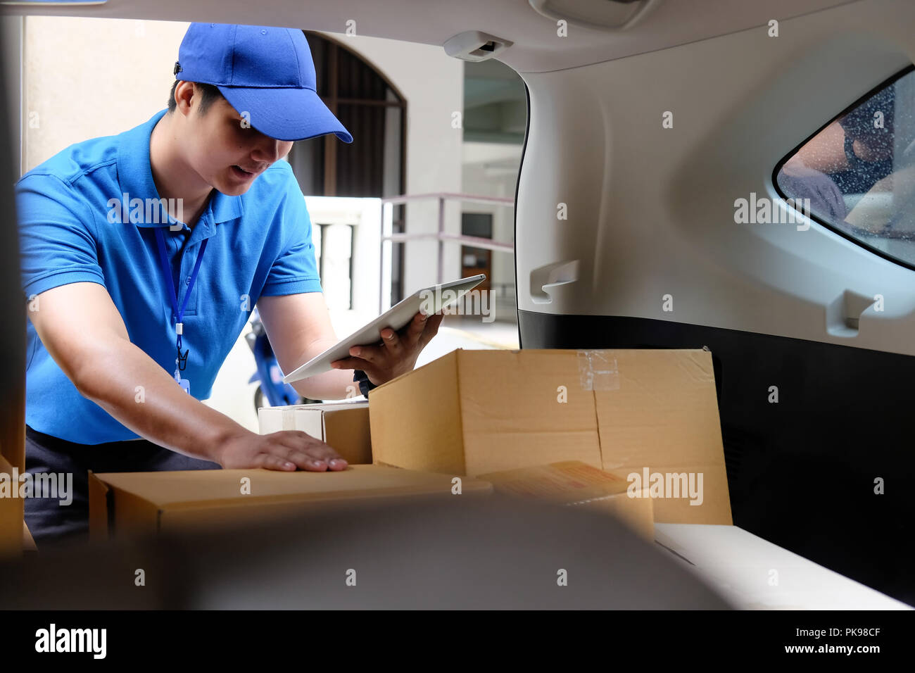 Delivery man working with box in car, Asian man working job. - Stock Image