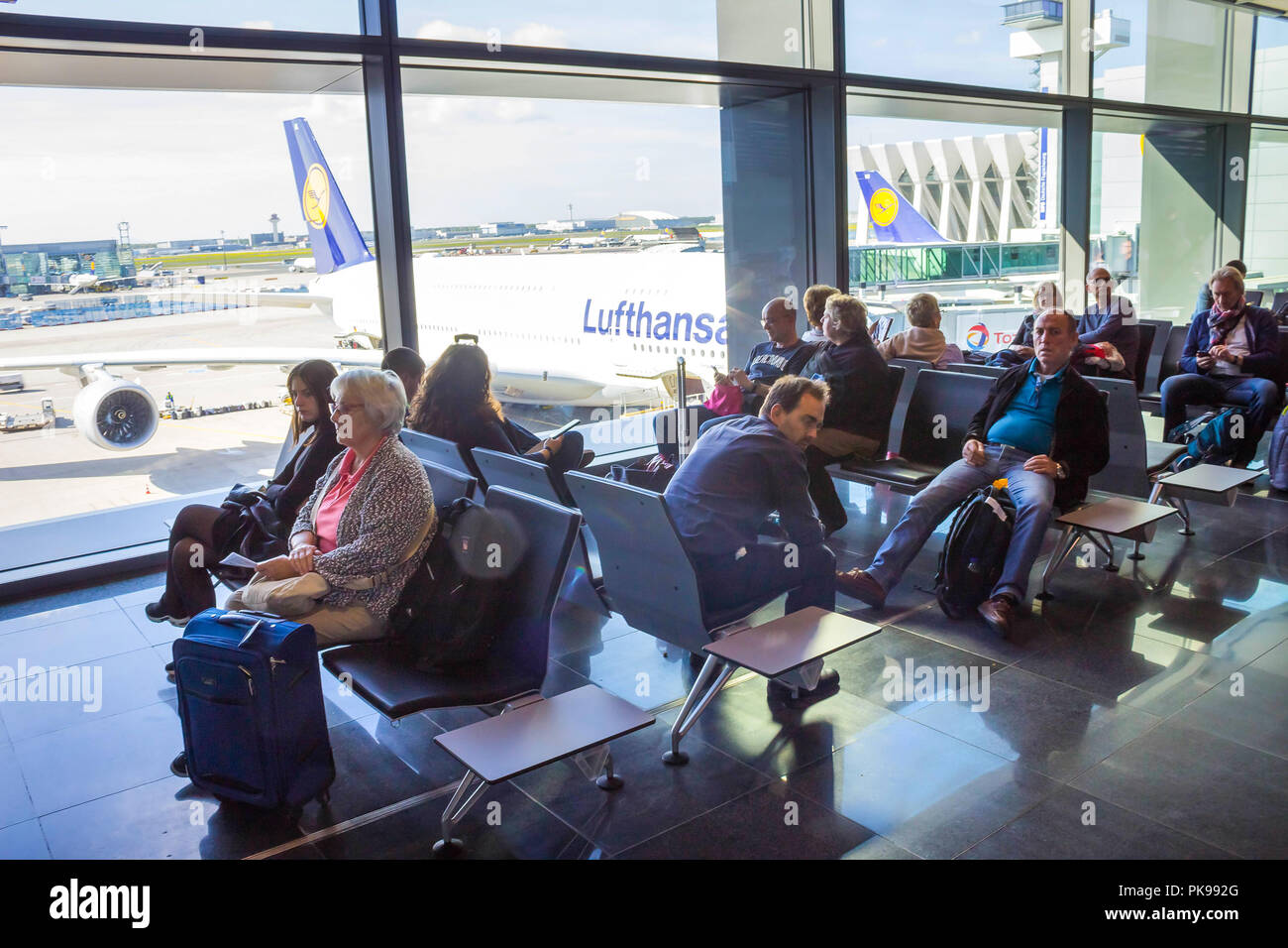 Frankfurt, Germany - April 28, 2018: passengers sitting and waiting for departure inside of Frankfurt Pearson Airport at Frankfurt, Germany on April 28, 2018 - Stock Image