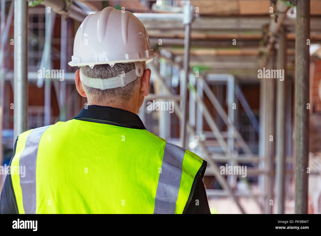 Rear view of male builder construction worker on building site wearing hard hat and hi-vis vest - Stock Image