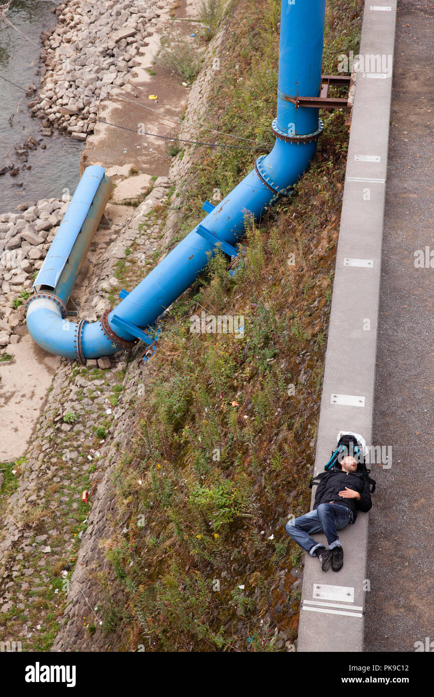 man takes a nap on the wall on the banks of the river Rhine in the district Deutz, sewage pipe, Cologne, Germany.  Mann macht ein Nickerchen auf der M - Stock Image