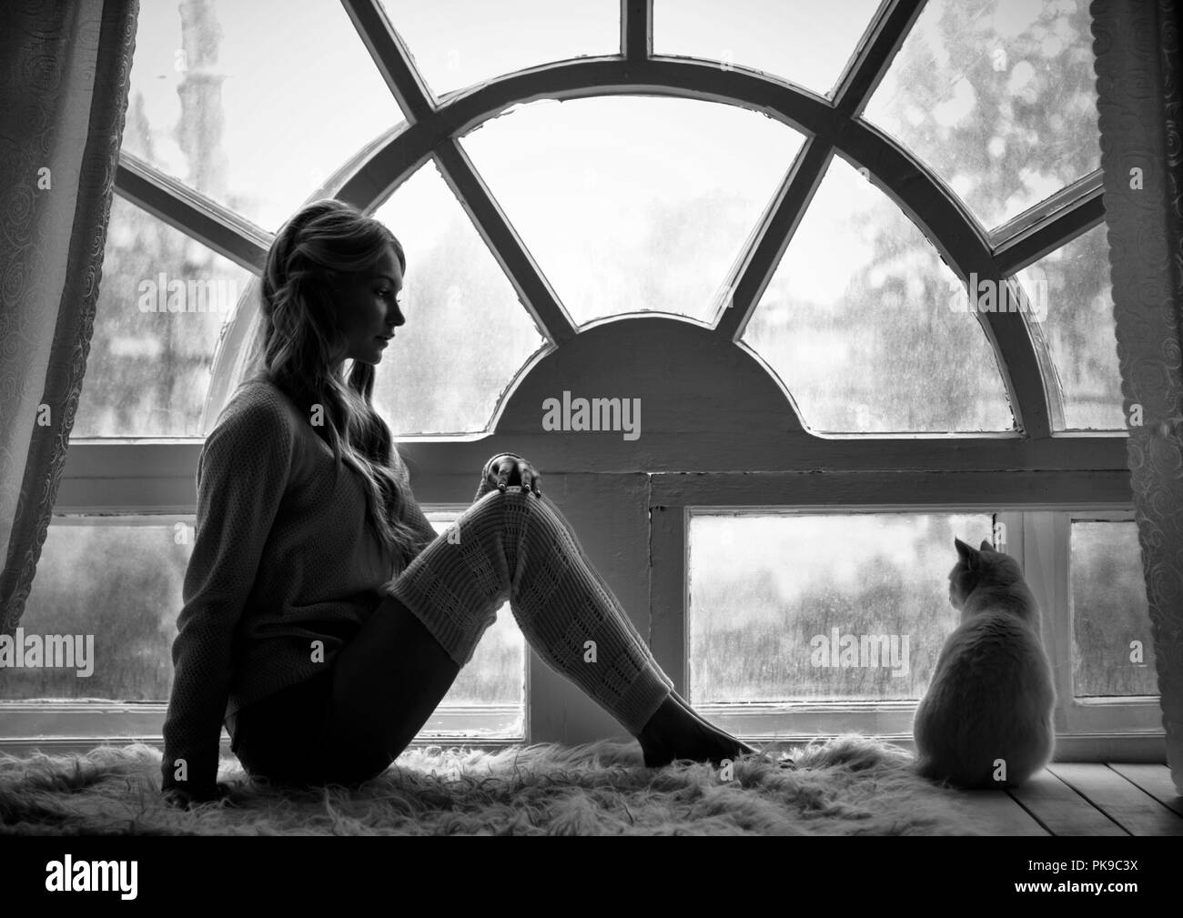 Art photo blond girl and white cat sitting at big old window during the rain romantic black and white photo loneliness and sadness in rain