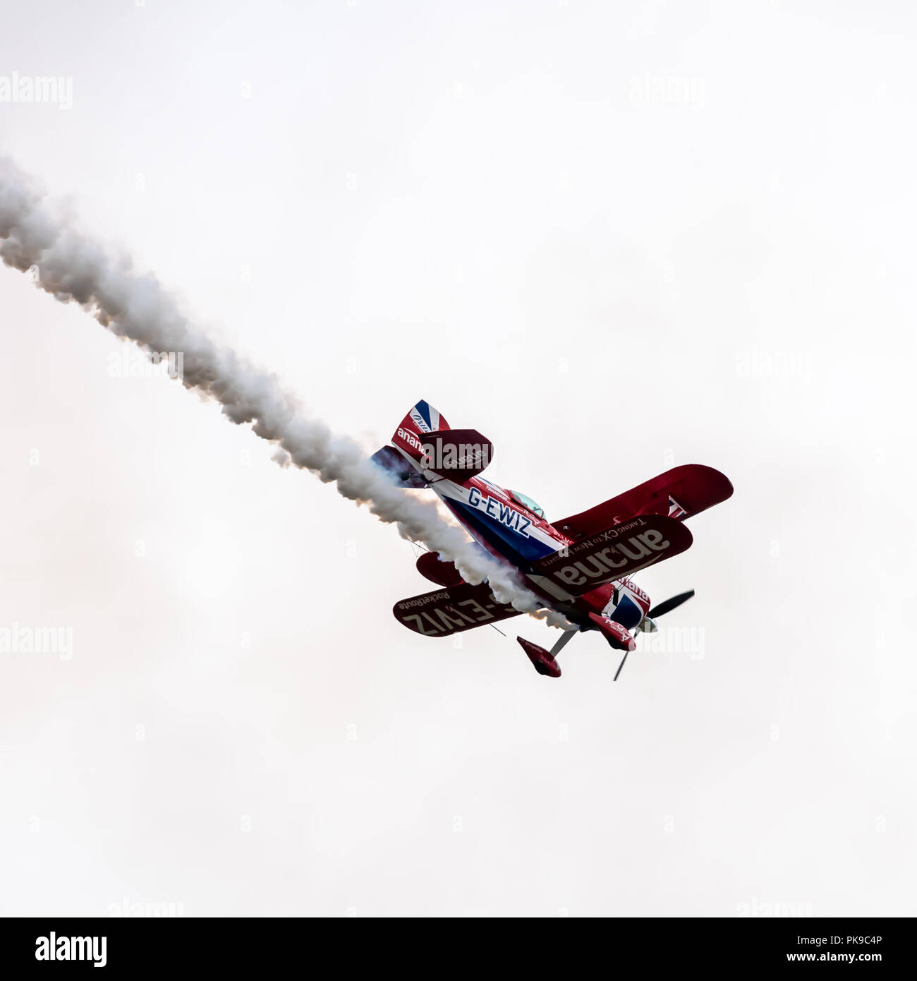 A Pitts Special S2S biplane with a highly modified. 8.5 ltre Lycoming 540 engine trails a plume of thick white smoke during a display - Stock Image