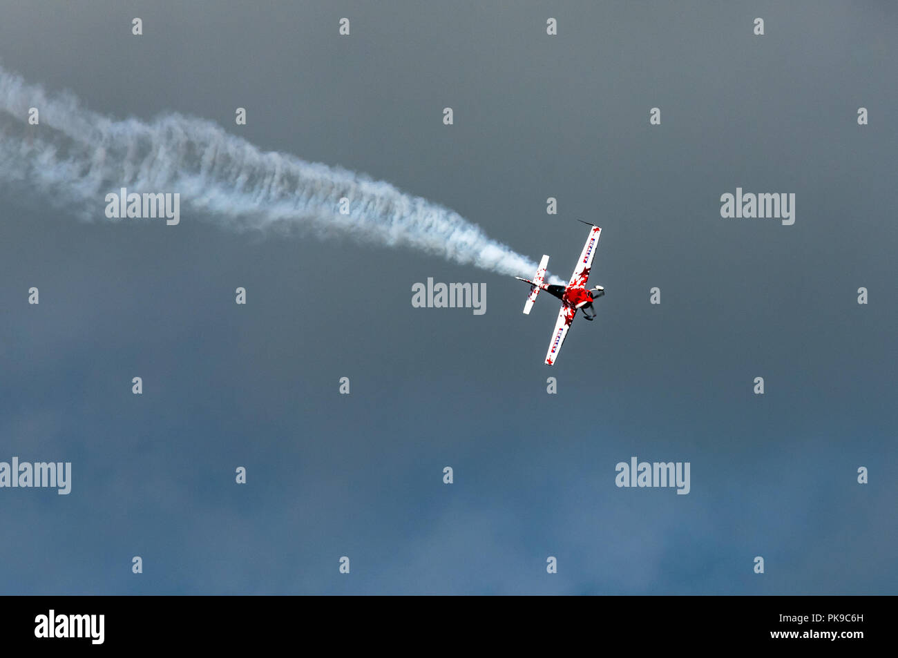 A plume of white smoke trails behind a G-Force Aerobatics Extra 300 monoplane during a display. - Stock Image