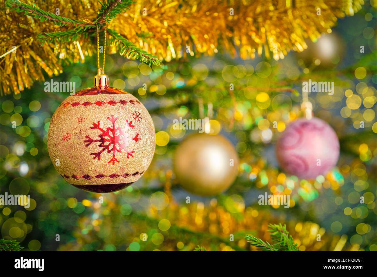 Christmas-tree decoration bauble on decorated Christmas tree bac - Stock Image