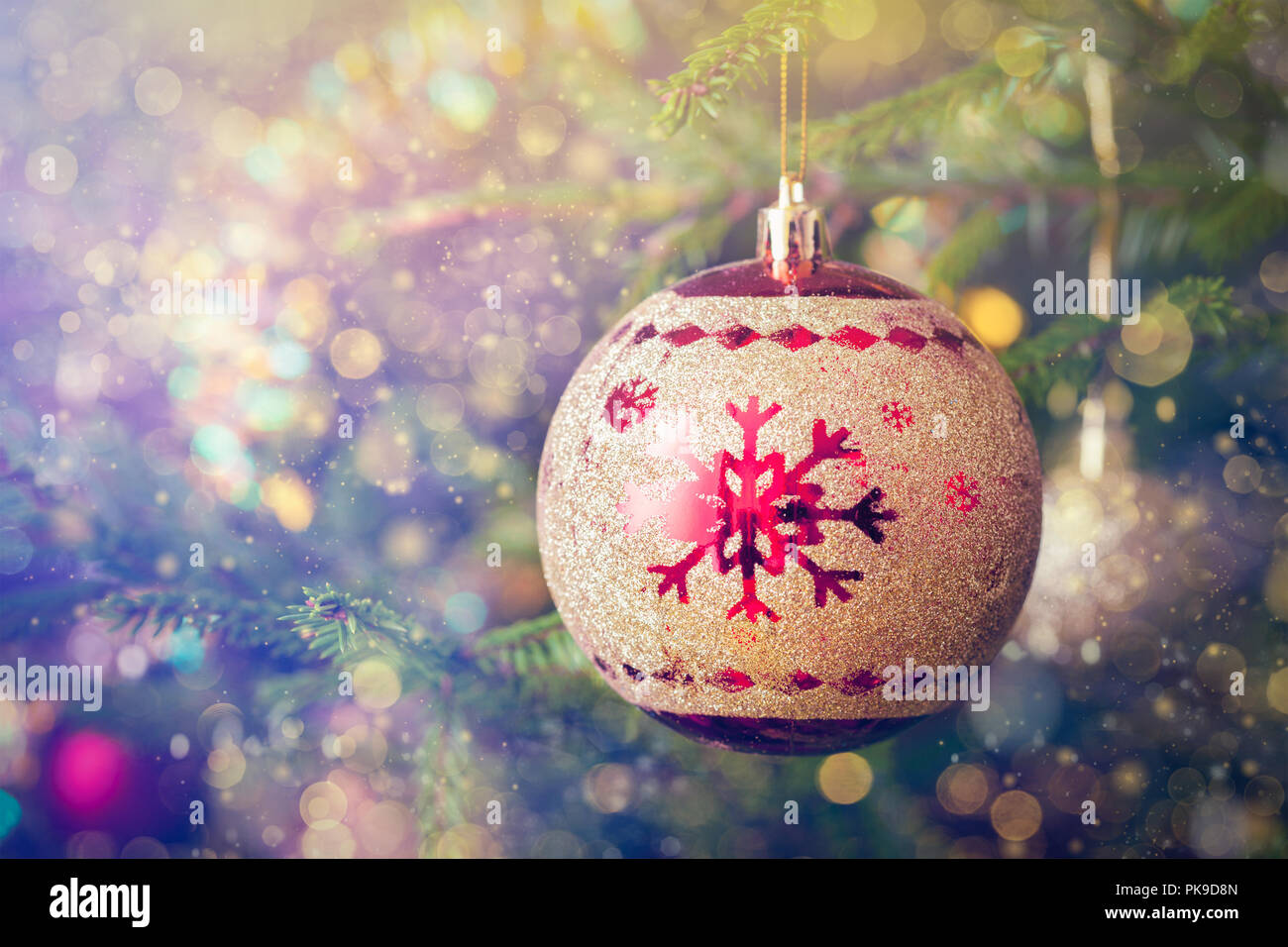 Christmas-tree decoration bauble on decorated Christmas tree bac - Stock Image