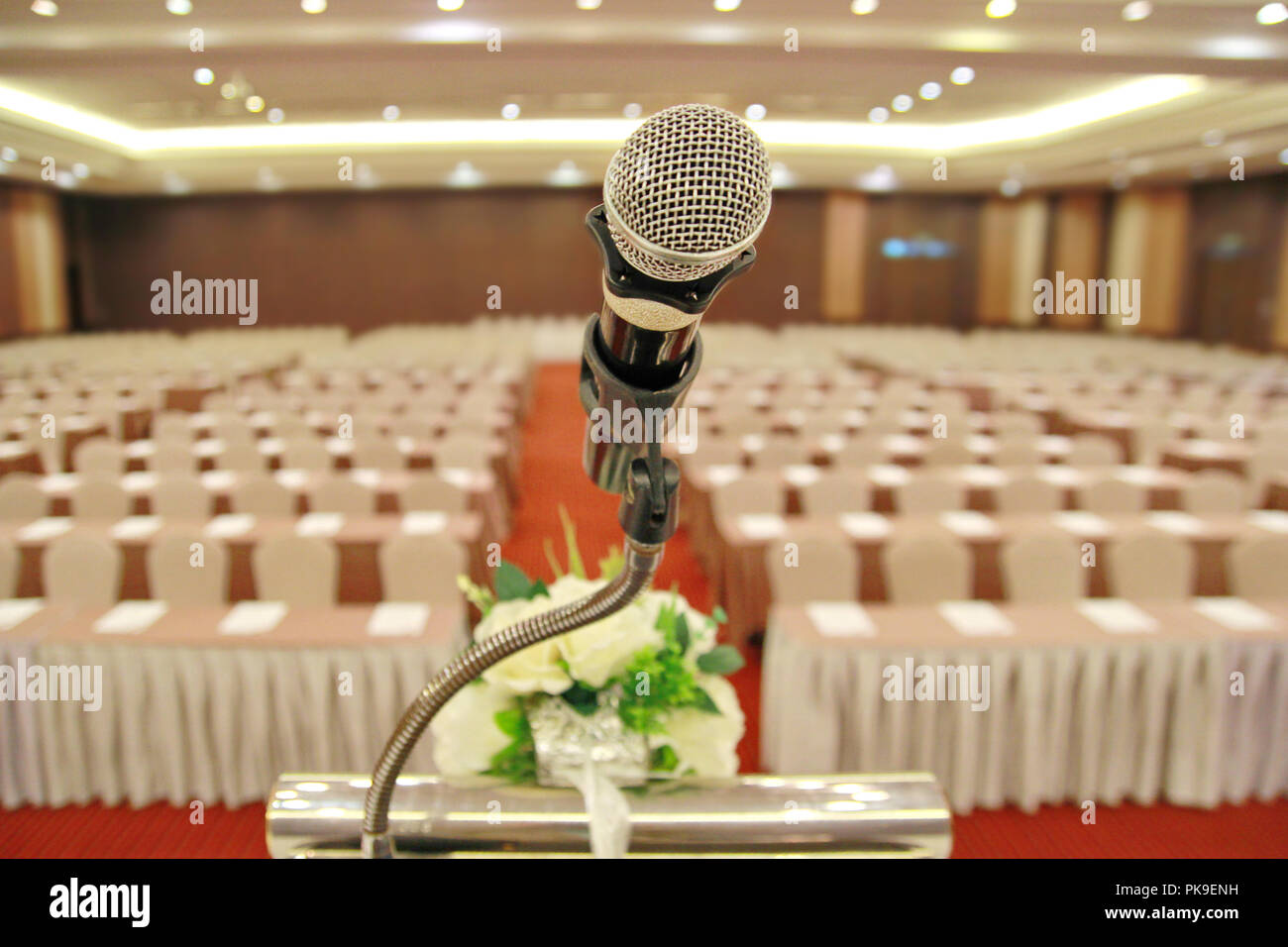 The microphone is located on podium stand at the center of the room is covered with a red carpet with a white tables cloth and chairs and prepare befo - Stock Image