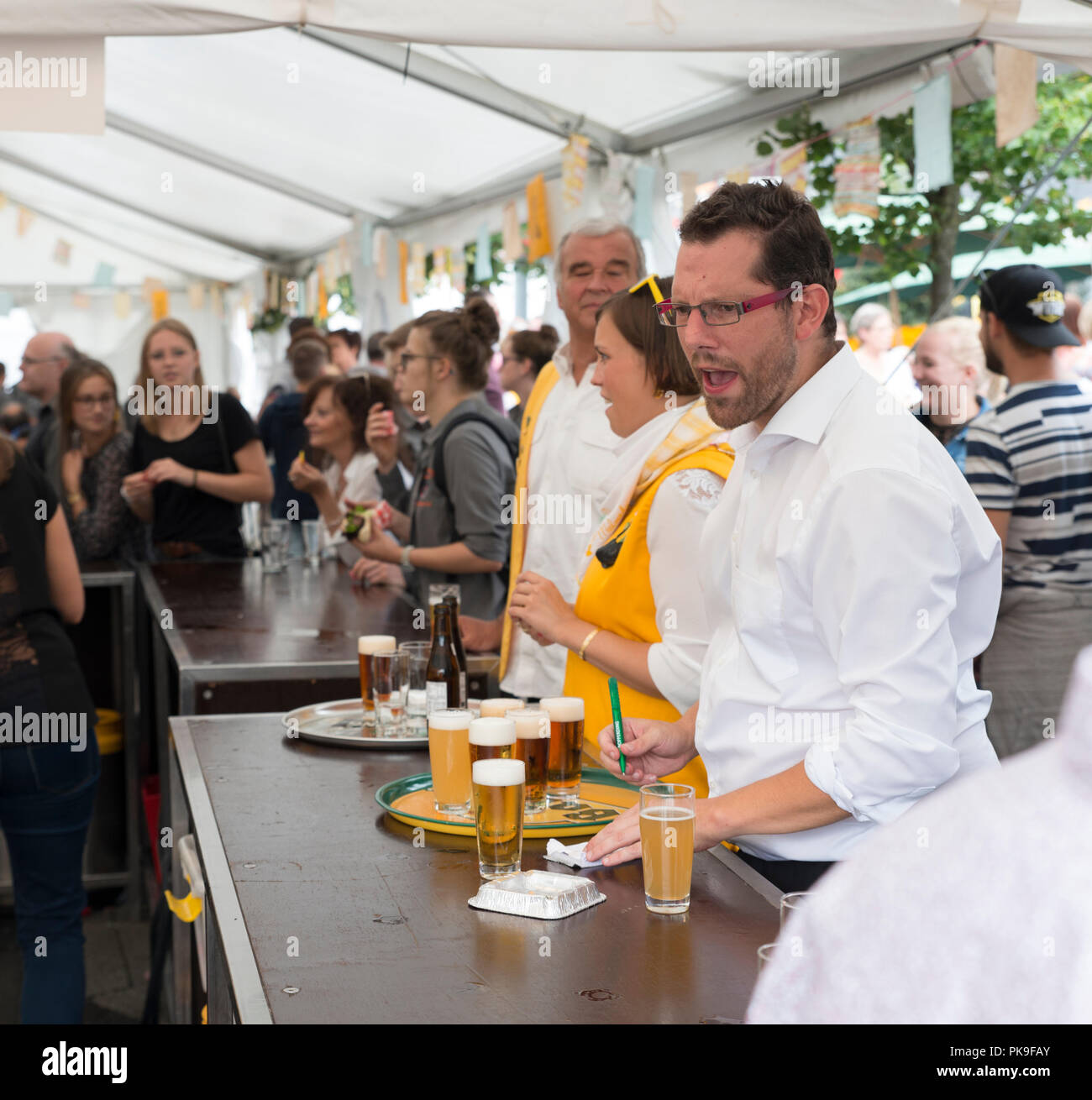 Malmedy,Belgium,15-Aug-2018:waiter at the bar calls for a beer during a event in Malmedy,In august there is big event with music and bars that is visisted also by lot of tourists Stock Photo