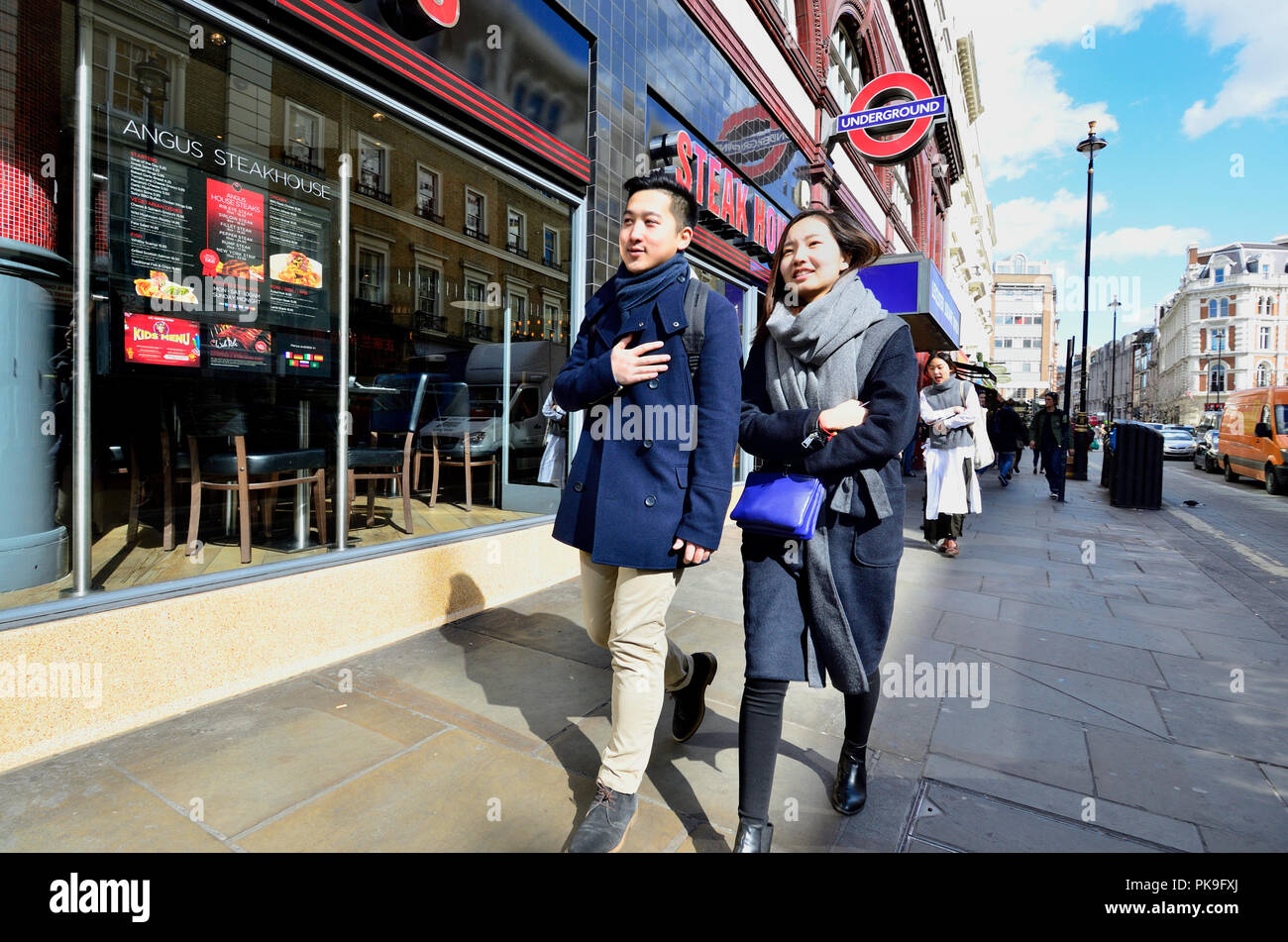 Young Chinese couple passing Leicester Square tube station. London, England, UK. - Stock Image