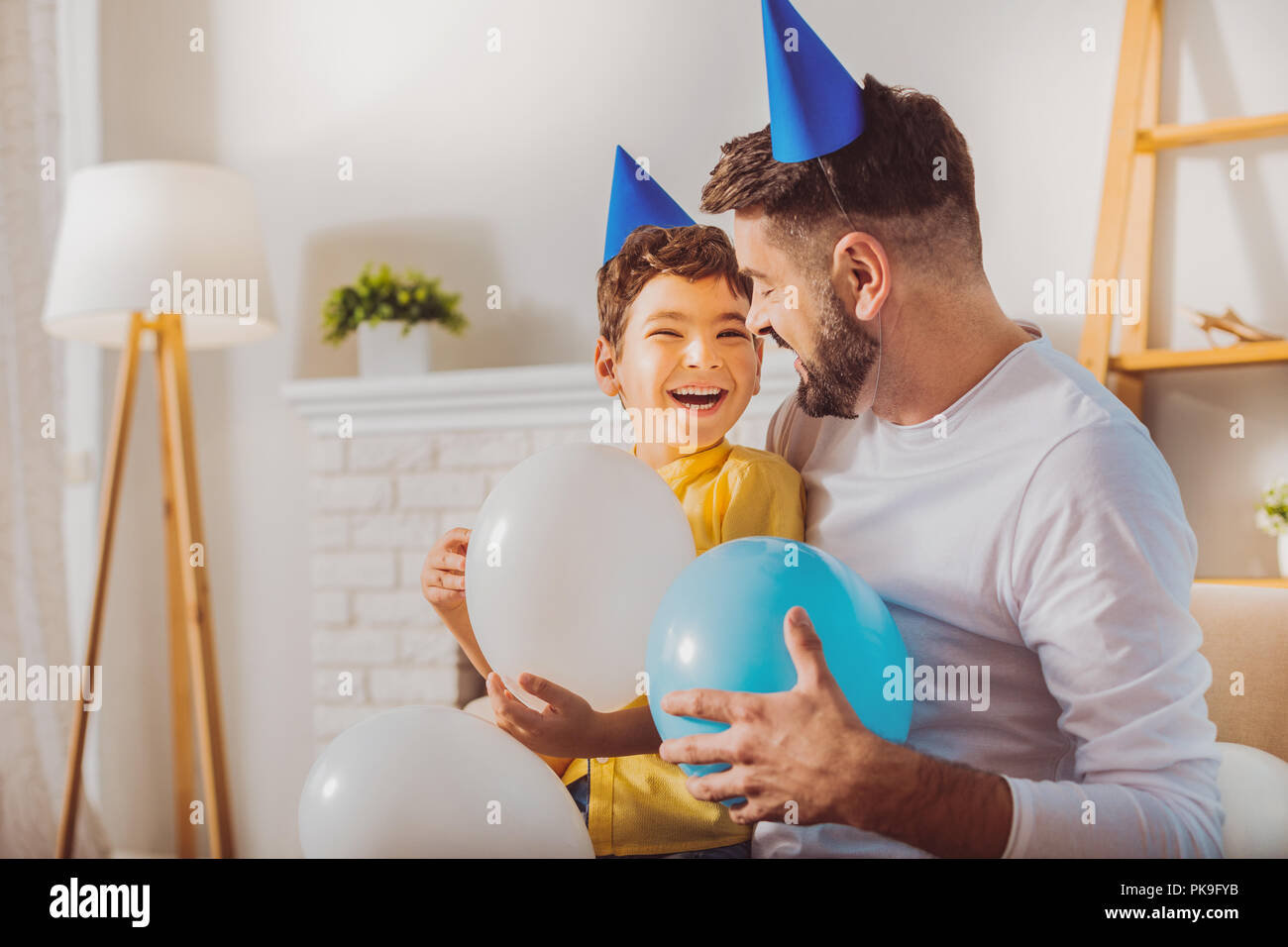 Merry charming boy and man having fun with balloons - Stock Image