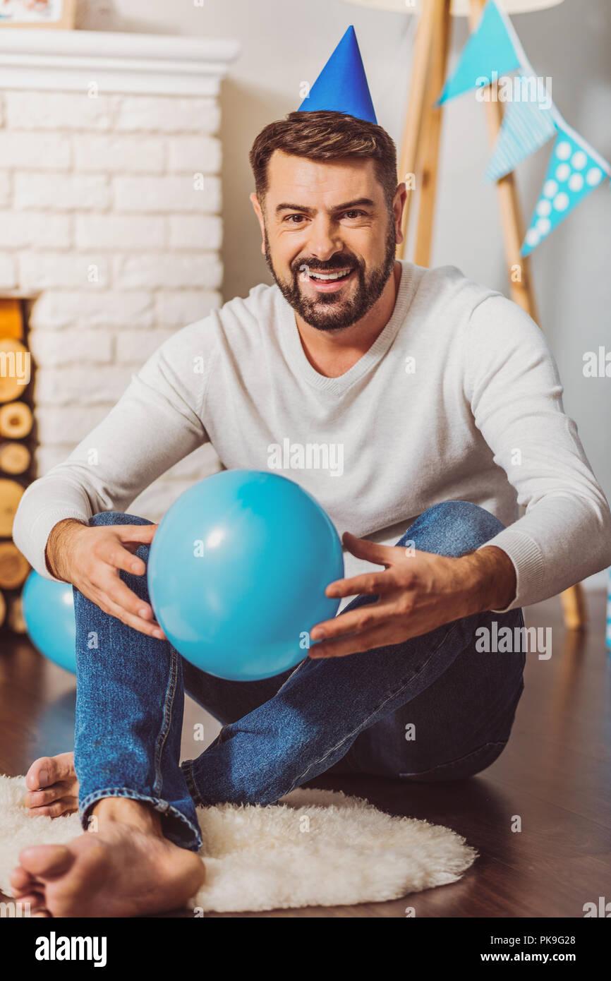 Handsome charming man playing with balloon - Stock Image