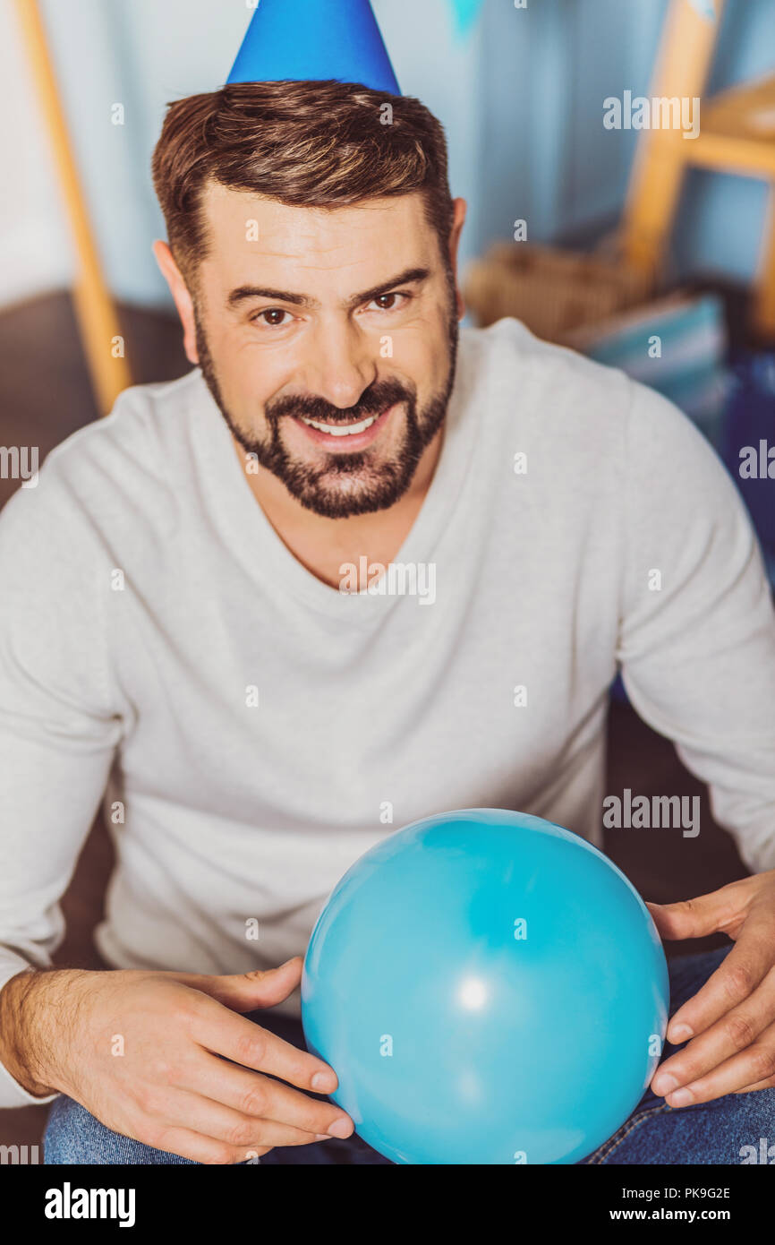 Joyful merry man toying with ballon - Stock Image