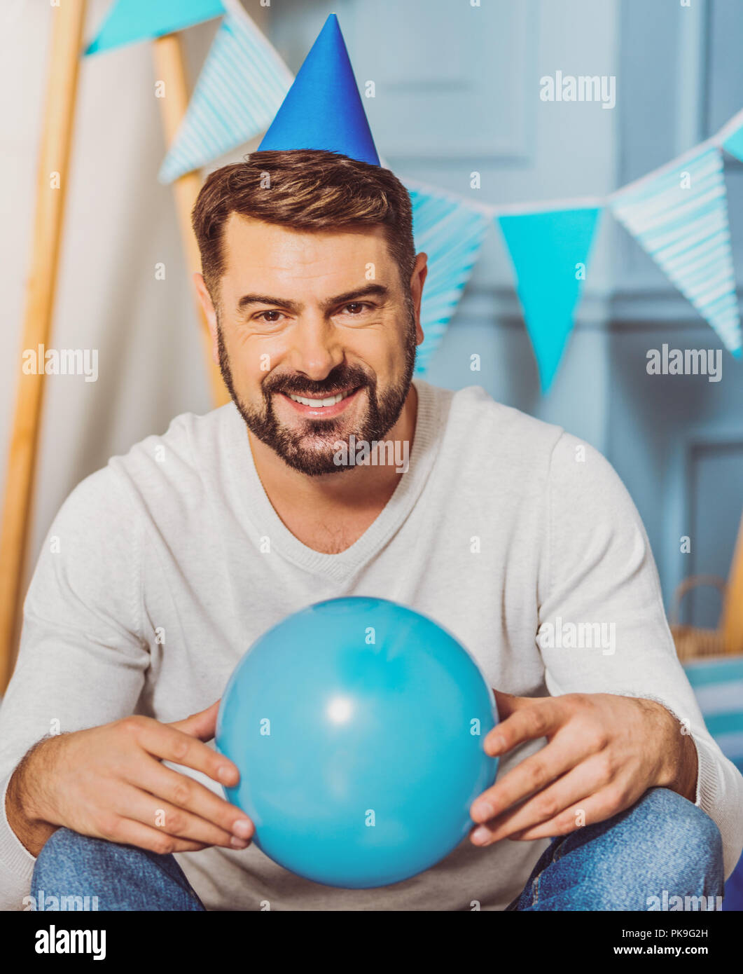 Handsome happy man monkeying with balloon - Stock Image
