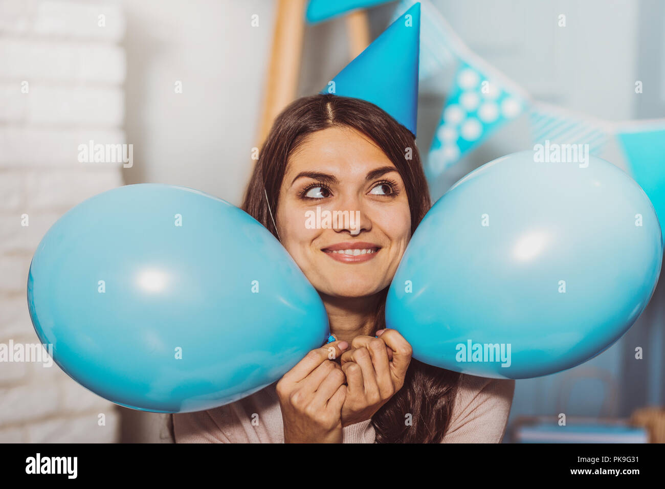 Pretty jolly woman dreaming about birthday party - Stock Image