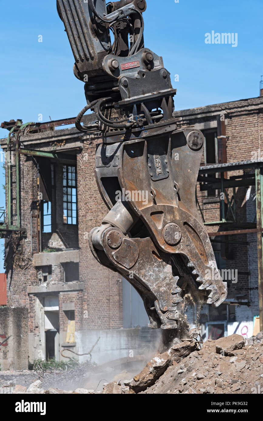 demolition grapple of an excavator on a construction site during demolition work. - Stock Image