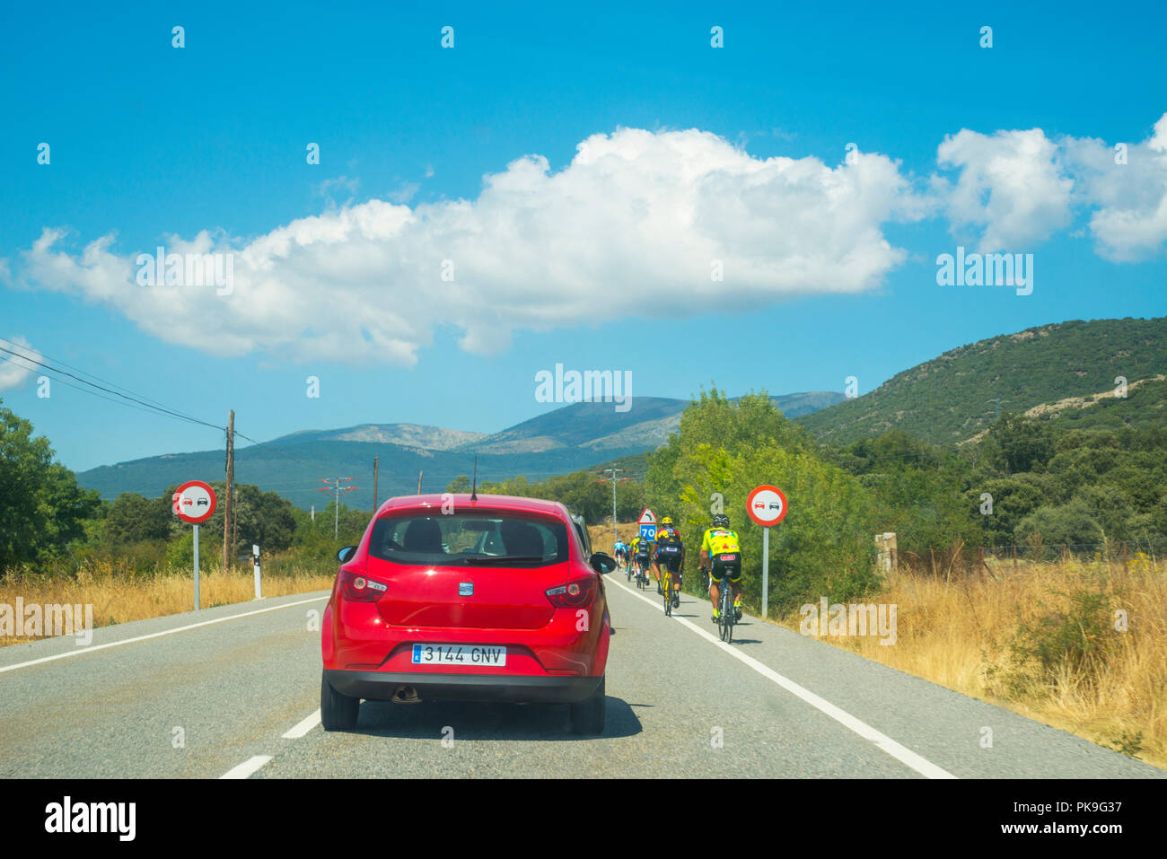Car overtaking a group of ciclists. - Stock Image