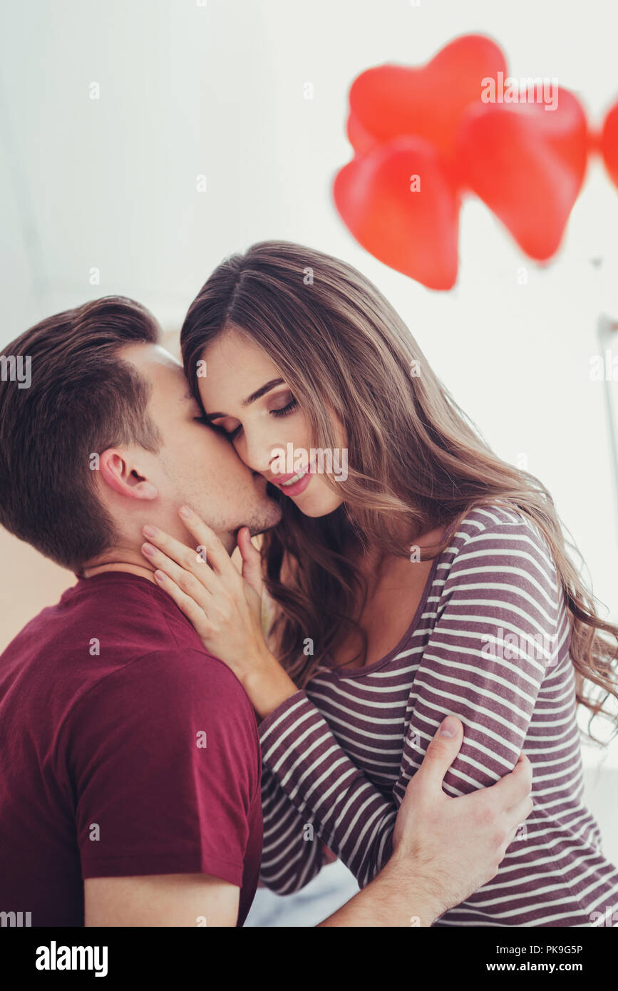 Portrait of young man kissing his amazing girlfriend - Stock Image
