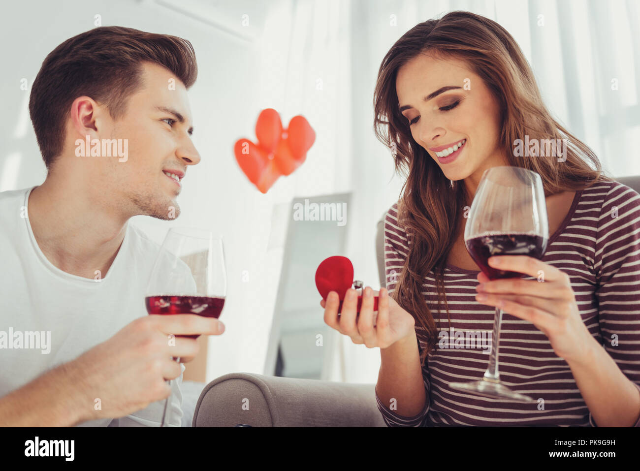 Portrait of adorable girl being pleased with boyfriends proposal - Stock Image