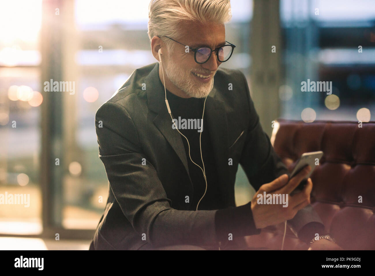 Mature businessman sitting in office lobby making video call with his smart phone. Caucasian man with white hair in office making video call. - Stock Image
