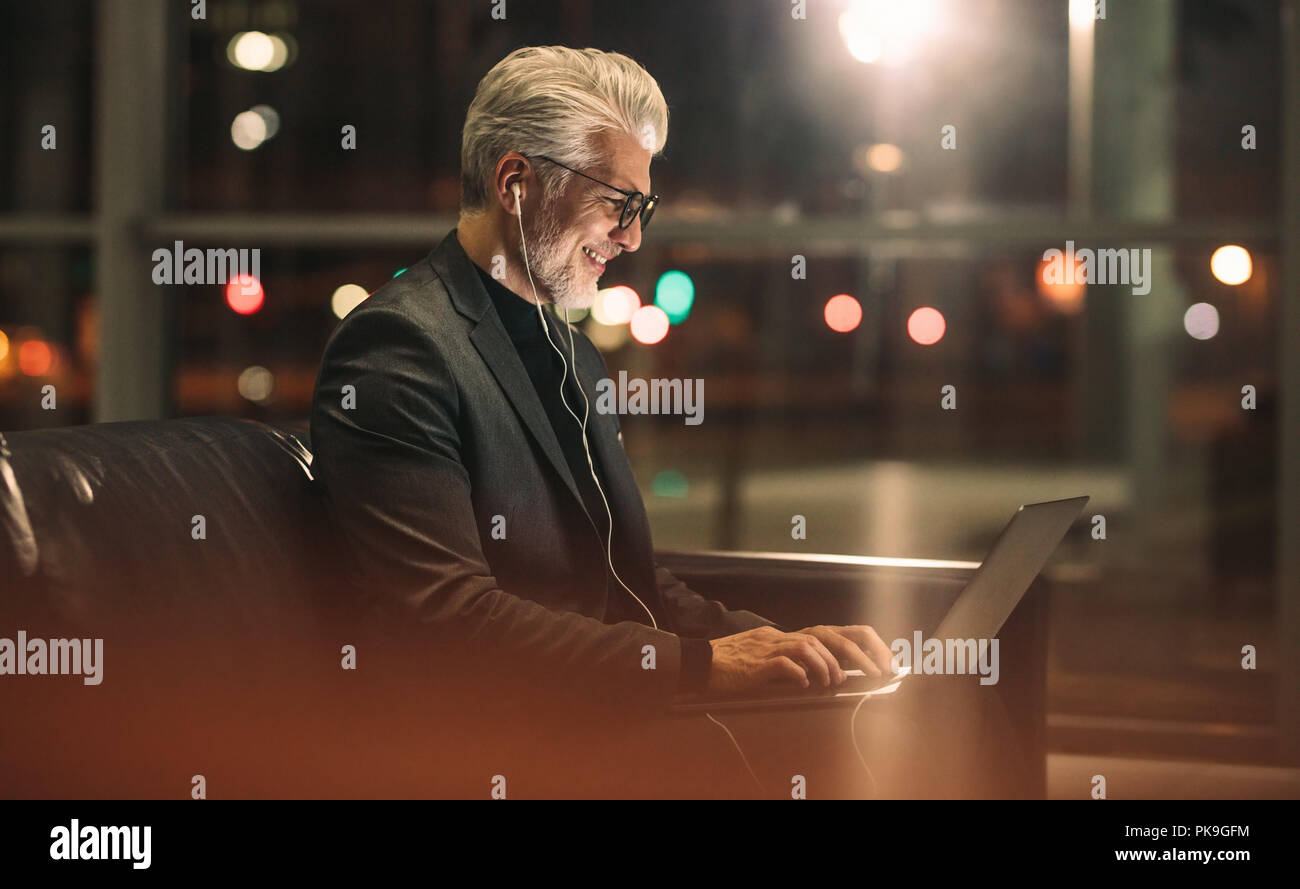 Happy mature man working late at office. Businessman using laptop in office lobby. - Stock Image