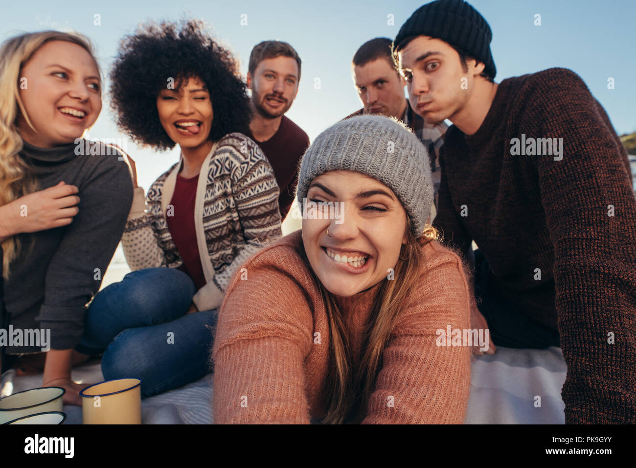Group of young people making funny faces while taking selfie on the beach. Young people enjoying together at the beach making a self portrait. - Stock Image