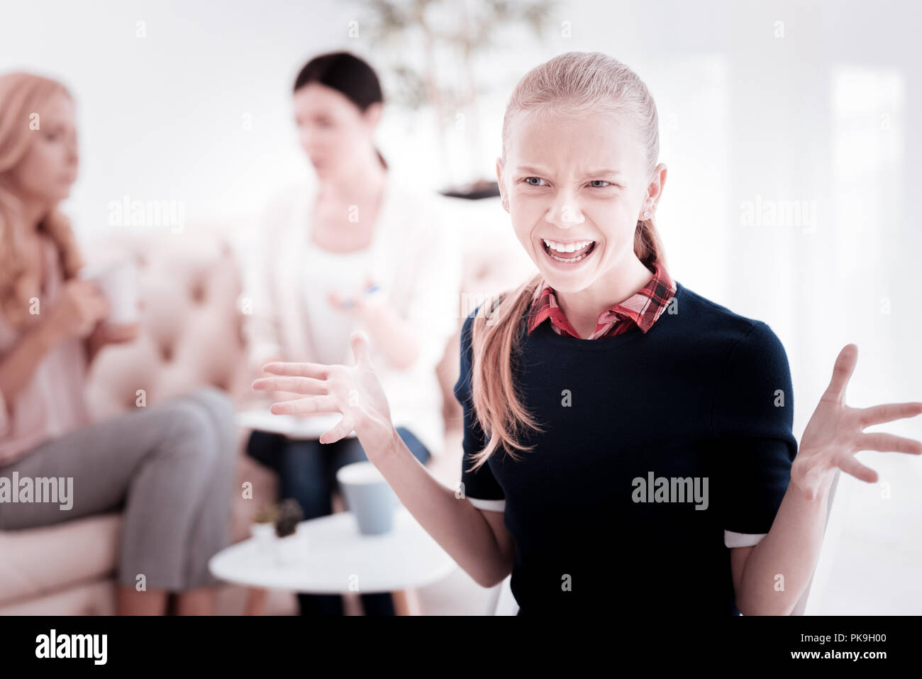 Emotional teenage girl shouting and feeling angry - Stock Image