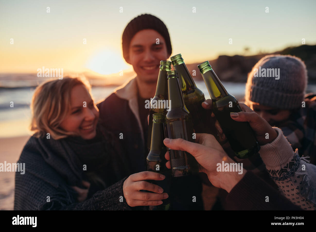 Young people toasting with beer bottles on beach. Group of men and women having drinks together at sea shore during sunset. - Stock Image