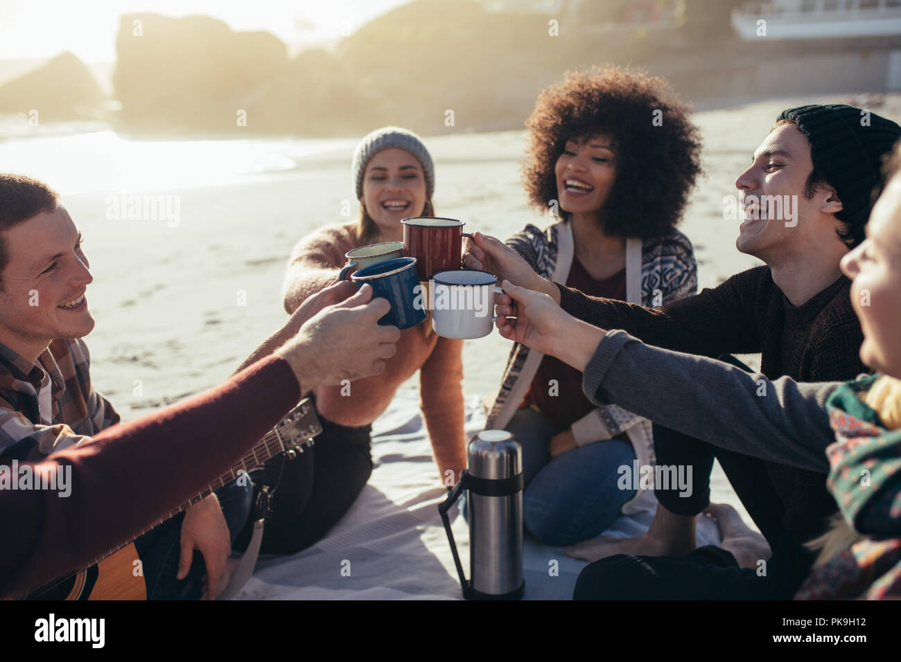 Group of multi-ethnic young people toasting coffee mugs on the beach. Group of friends spending time together at the beach having coffee. - Stock Image