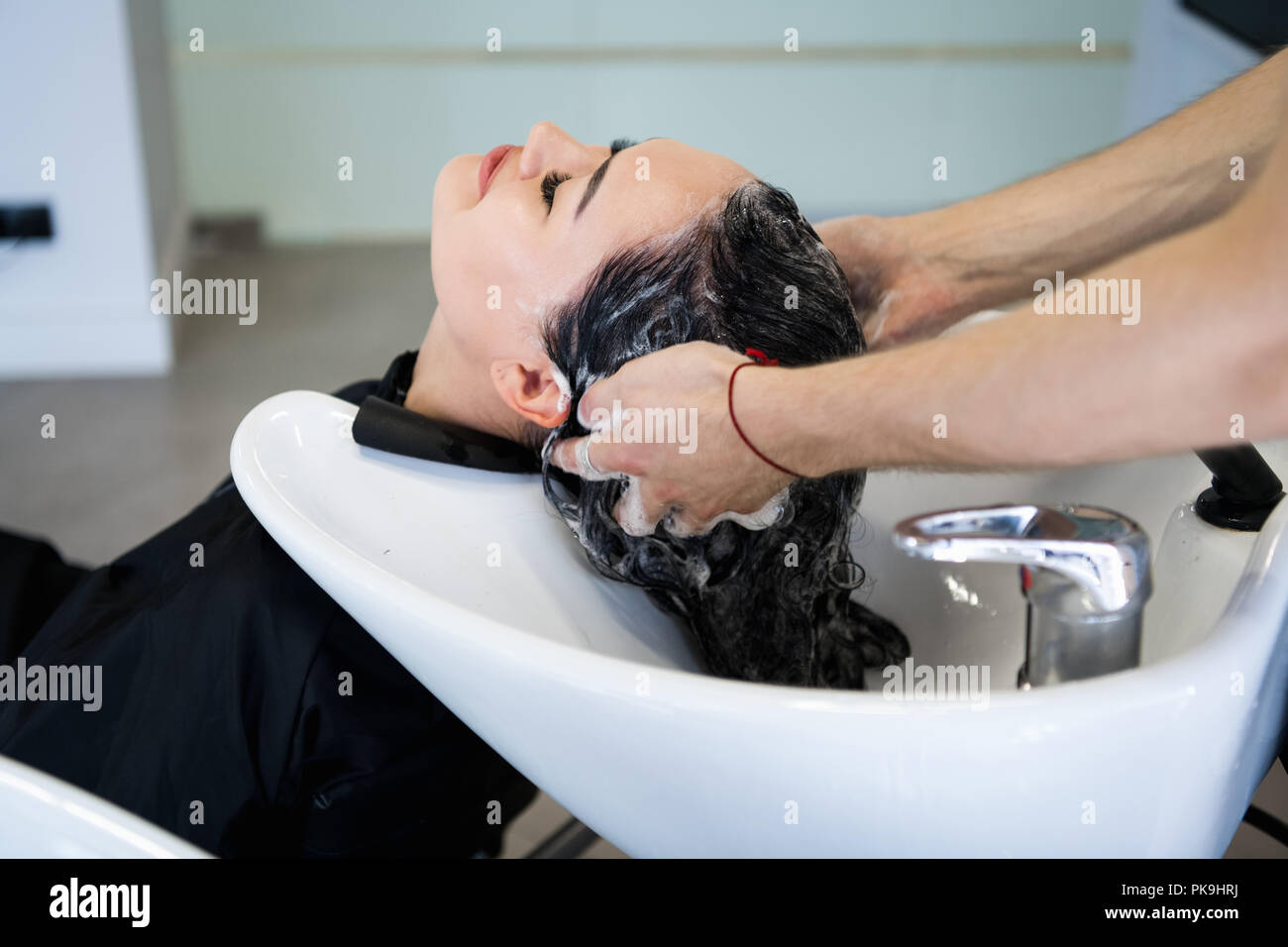 Beautiful brunette washes hair in a beauty salon - Stock Image