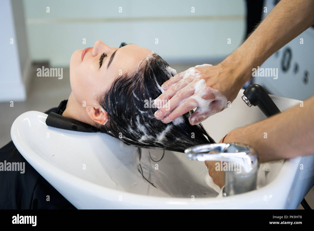 Unrecognizable professional hairdresser washing hair to her client. Beautiful hairdresser washing hair to her client lady in hairdressing saloon. Client sitting with her eyes closed. - Stock Image