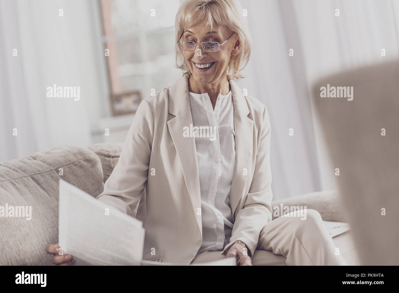 Retired writer wearing glasses reading feedback letters - Stock Image