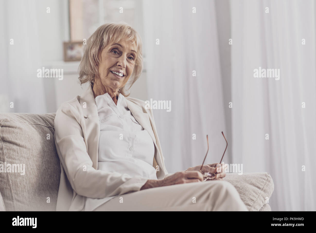 Appealing woman with facial wrinkles feeling thoughtful - Stock Image