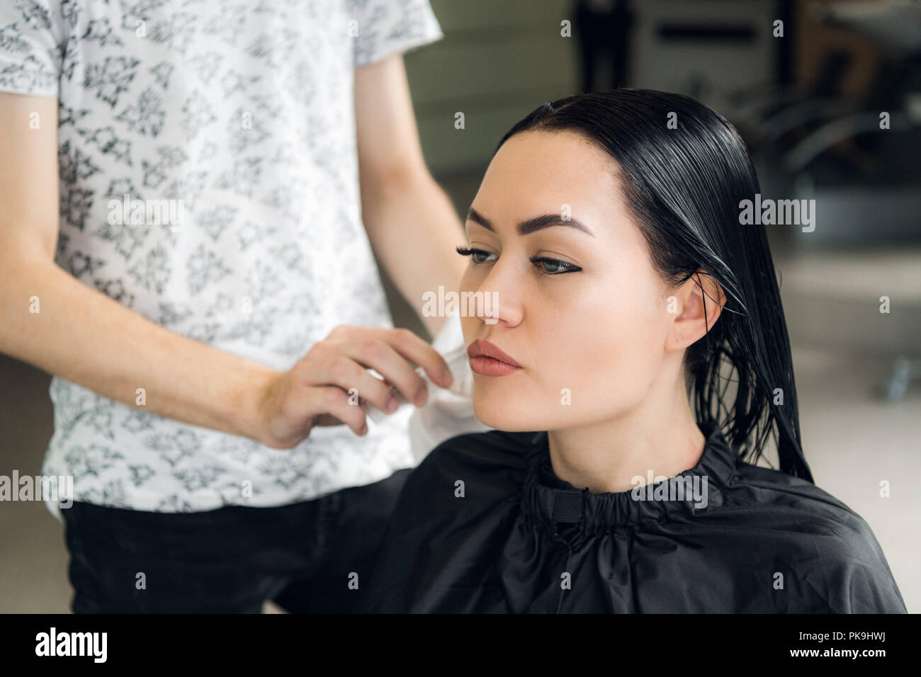 Hairdresser cutting woman's hair in salon, smiling, front view, close-up, portrait Stock Photo