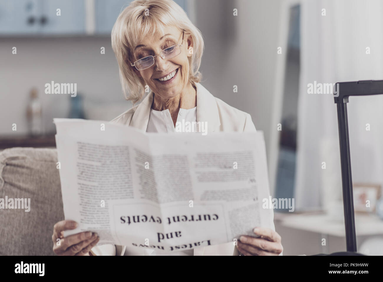 Smiling elderly woman reading info about current events - Stock Image