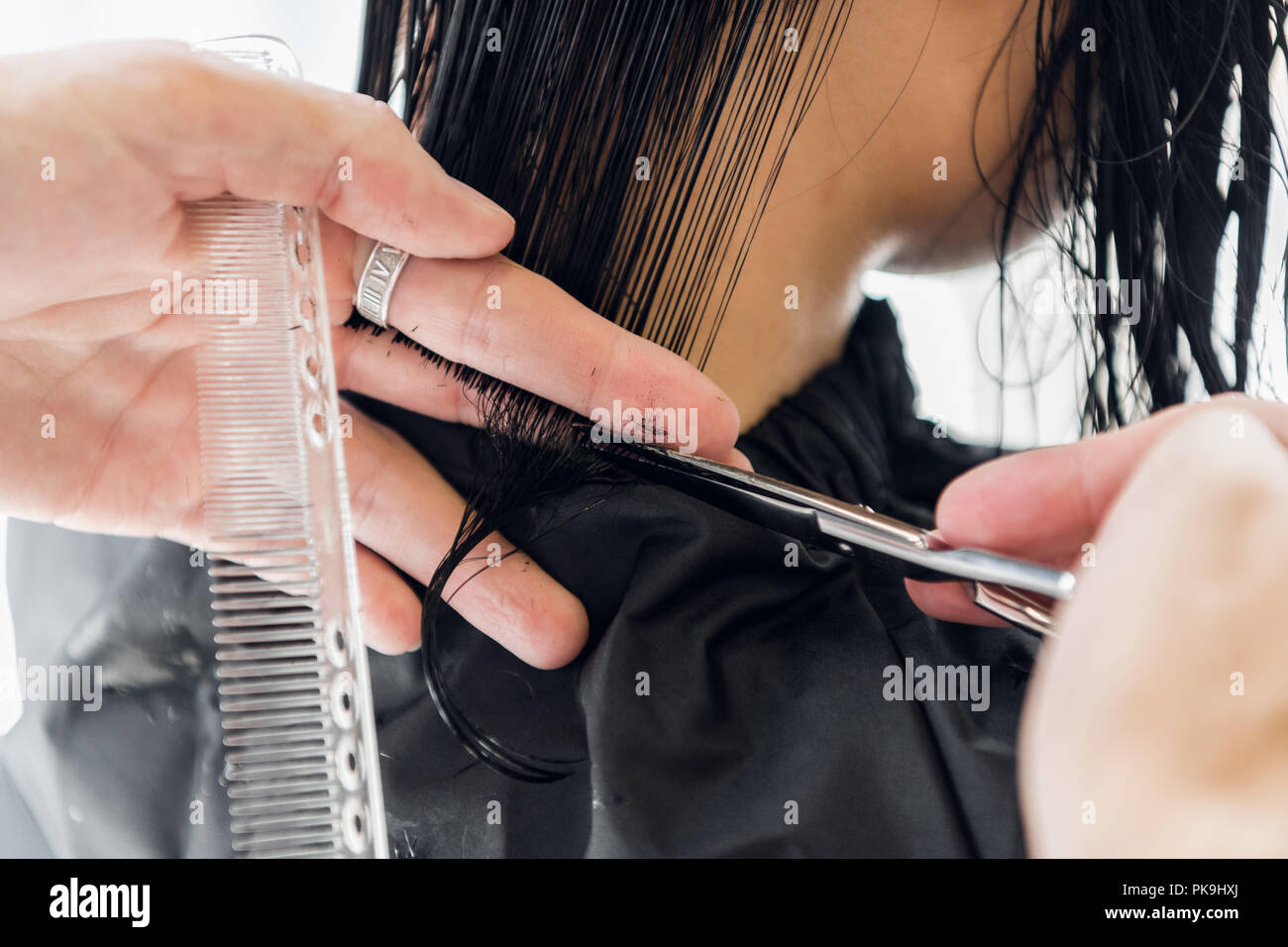 Man's hands cut and comb female dark brown hair in a beauty salon with mirrors - Stock Image