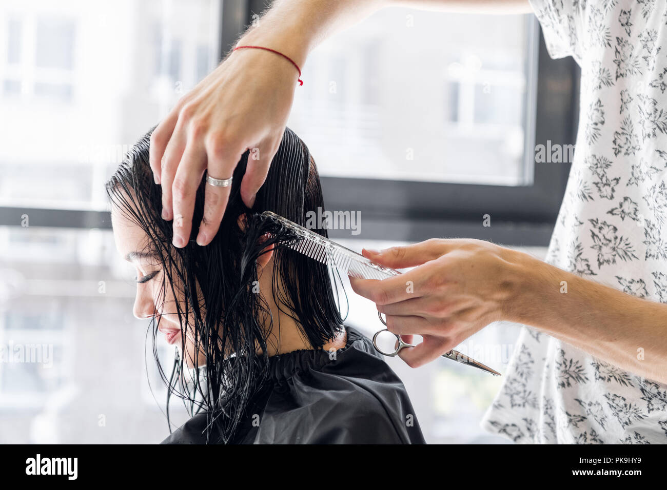 Young beautiful woman having her hair cut at the hairdresser's. Young male hairdresser smiling and making hairstyle to the customer. - Stock Image