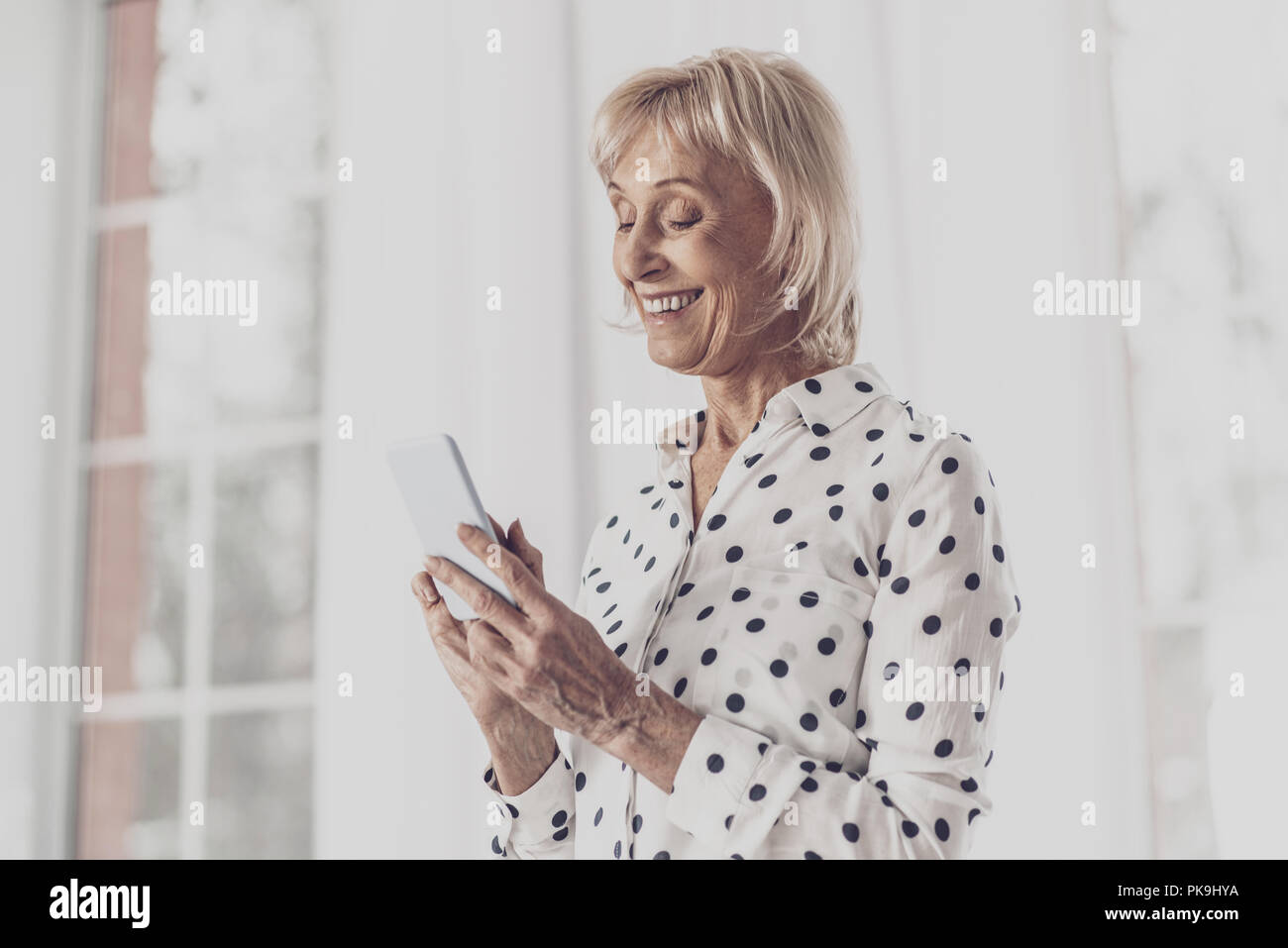 Elderly lady with facial wrinkles feeling wonderful - Stock Image
